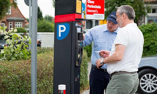 DB Bahnpark Mitarbeiter unterstützt Kunden am Parkscheinautomat