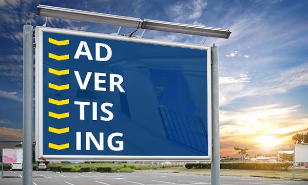 """Große Werbetafel mit Schriftzug """"Advertising"""" auf einem leeren Parkplatz"""