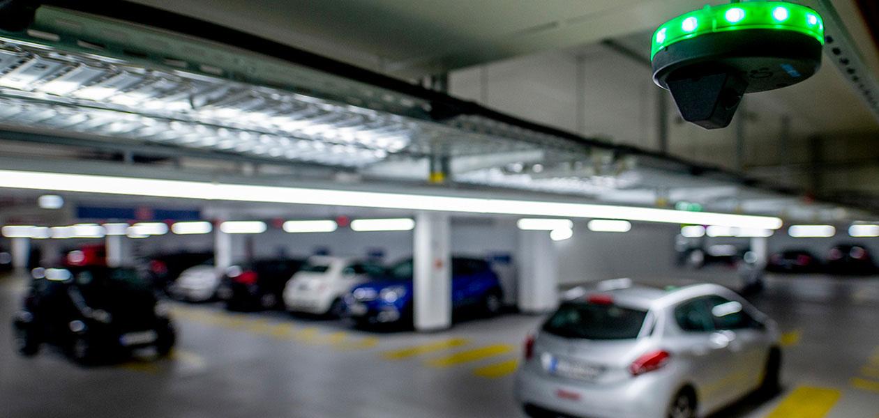 Parkplatzsensor mit grünen LED-Lampen vor einem unscharfen Parkhaushintergrund