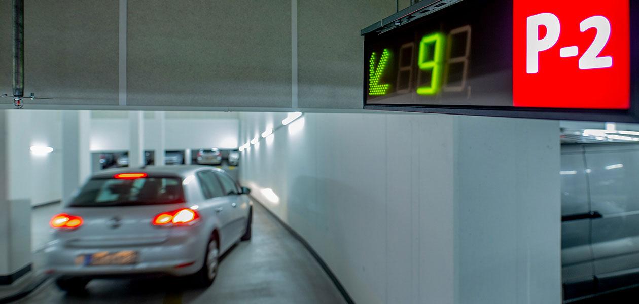 Digitale Anzeigetafel zu freien Parkplätzen auf Parkebene 2 mit verschwommenem Auto im Hintergrund