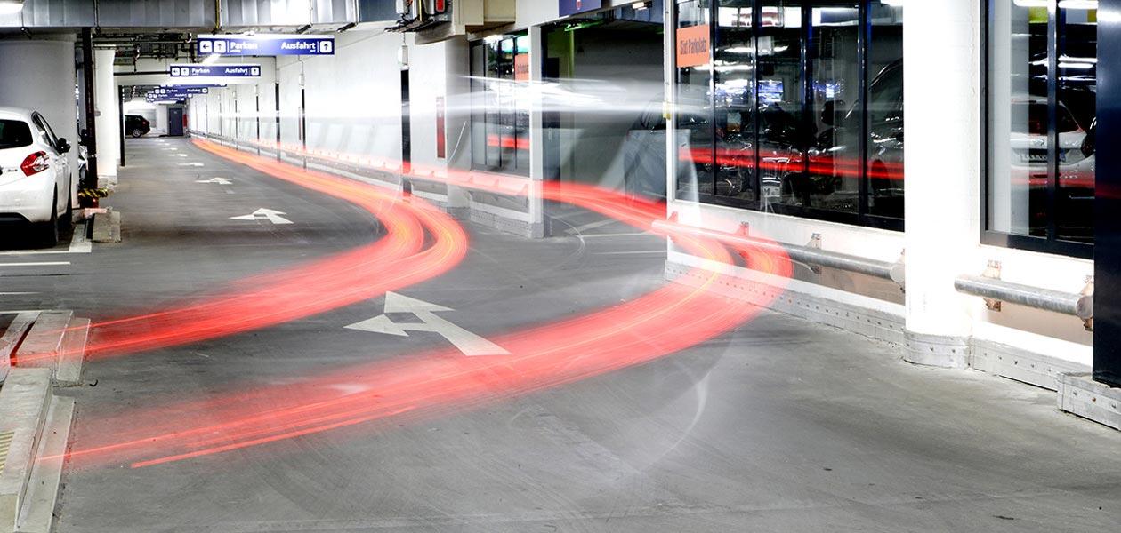 Weg in Richtung Ausfahrt in der Tiefgarage Stachus; durch Mehrfachbelichtung schweben Rücklichter eines Autos als rote Streifenspuren im Raum